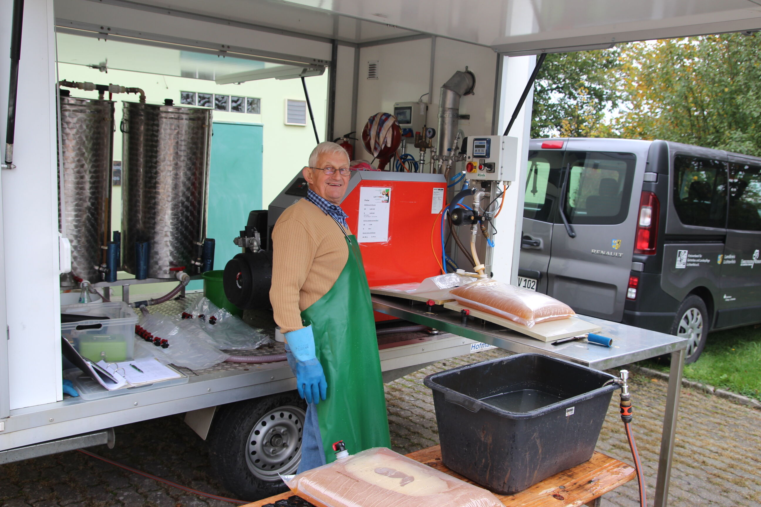 Georg Hofmann vom Team des Kreisverbandes füllt am Saftmobil den frisch gepressten Saft in die Bag-in-Box-Beutel ab. Foto: Umweltstation Weismain/ Mic