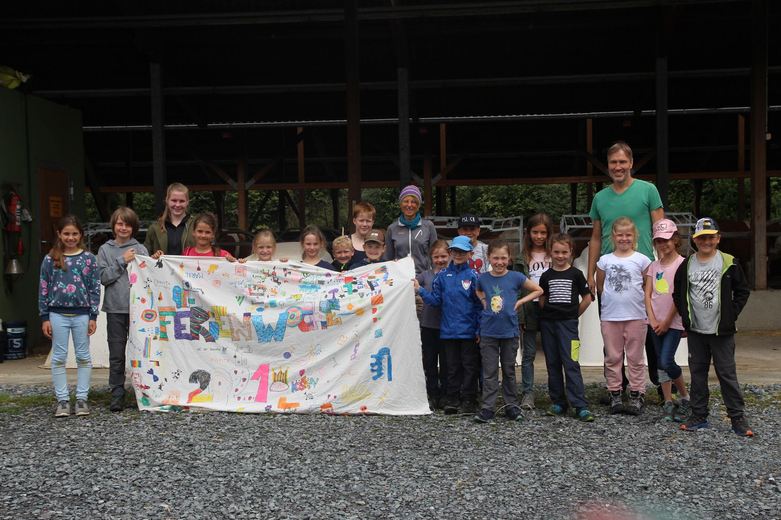 Die 16 Kinder, die an der Ferienwoche auf dem Erlebnisbauernhof Hofmann in Kösten teilgenommen haben, mit ihrer Freizeitfahne und den Betreuern Joseph